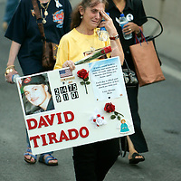 Barbara Tirado carrying a picture of her son David killed in the World Trade Center attack arrives at the site of the disaster for a memorial service on the fourth anniversary of the tragedy in New York September 11, 2005.