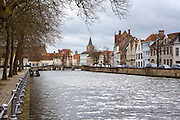 A patch of sun brightens a canal in Bruges on a grey day in spring