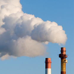 A power plant emits smoke plumes into the crystal clear blue sky on a cold winter day.