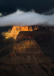 Clouds hover over the many rock formations found in the depths of the Grand Canyon.