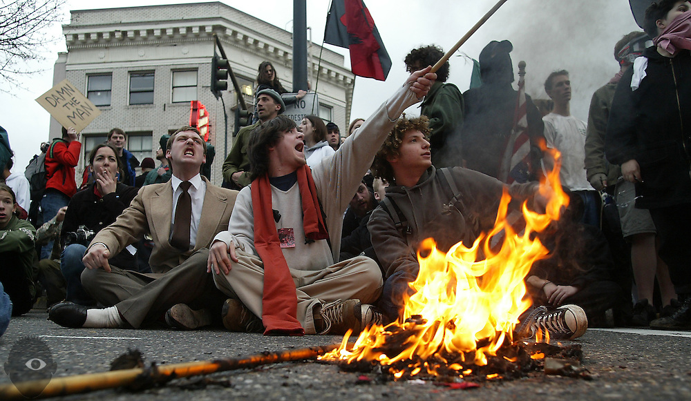 Protesters shout out anti-war, anti-government remarks while burning flags at the intersection of W. Burnside and 2nd Ave. An estimated 40,000 took to the streets of downtown Portland Saturday for an anti-war protest and march.