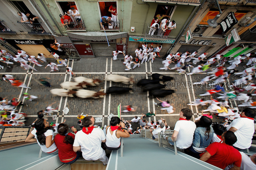 PAMPLONA, SPAIN - JULY 09: Revellers run with Valdefresno's ranch fighting bulls at Calle Estafeta during the fourth day of the San Fermin Running Of The Bulls festival, on July 9, 2013 in Pamplona, Spain. The annual Fiesta de San Fermin, made famous by the 1926 novel of US writer Ernest Hemmingway 'The Sun Also Rises', involves the running of the bulls through the historic heart of Pamplona, this year for nine days from July 6-14.  (© Pablo Blazquez)