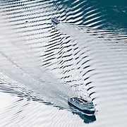 Ferry boats make wake patterns in Geirangerfjorden (the Geiranger fjord), a stunningly beautiful 15-kilometer (9.3-mile) long branch of Storfjord (Great Fjord, the fifth longest in Norway). Geirangerfjord is one of Norway's most visited tourist sites and has been listed as a UNESCO World Heritage Site since 2005. Take the car ferry for an impressive sightseeing trip between Geiranger and Hellesylt, in Stranda municipality, Sunnmøre region, Møre og Romsdal county, Norway.