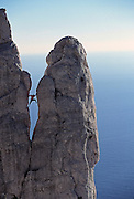 "A male rock climber ""chimneys"" up the side of a rock tower in the Calanques, a rock climbing area near Cassis and Marseilles in the South of France."