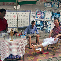 Asia, China, Chongqing. Traditional Chinese medicine cupping procedure on street in Chongqing.