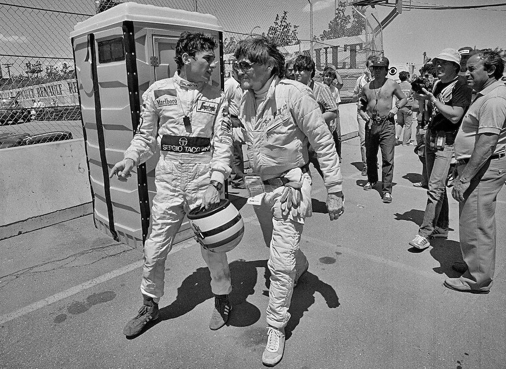 Brazilian Formula One driver Ayrton Senna is attended to by trackside medical personnel at the 1984 Detroit Grand Prix. Senna's Toleman-Hart had lost its brakes on the long front straight during practice and Senna collided with the tire barrier in Tune One. He was unhurt, but during the race, the Toleman sheared off its right rear wheel in the same place, and Senna met the tire wall a second time.<br /> <br /> Senna had already set the Formula One season afire by getting championship points in only his second race and barely missing his first Grand Prix victory at a streaming-wet Monaco Grand when the race was stopped due to rain just as he passed leader Alain Prost's McLaren.<br /> <br /> Within two months, he would be censored by Toleman for negotiating his next year's contract without giving Toleman first right of refusal, and leave for Lotus in 1985. <br /> <br /> He never visited the Detroit tire barriers again, but would go on the win that Grand Prix three times in a row, and collect three World Championships and total victories before tragically dying in a 1992 crash at the San Marino Grand Prix. Due to his death, Formula One would completely review and redesign safety measures and construction of its cars. As of 2013, he would remain the last Formula One driver to lose his life in a car during a Formula One event.