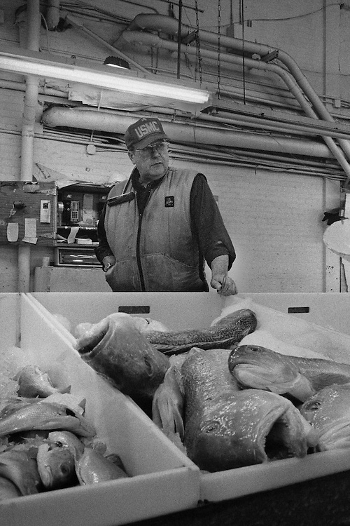 This man is selling fish. The boats are unloaded at midnight and buyers from restaurants walk around the various stalls buying food for the day. The market hours were midnight to 8 am each day. The Fulton Street Fish Market operated in this location near the Brooklyn Bridge for 183 years until it was relocated to the Bronx in 2005.