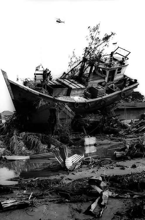 A fishing boat is violently deposited inland by the Tsunami that devastated Banda Aceh. Inside is the body of one of it's crew members.