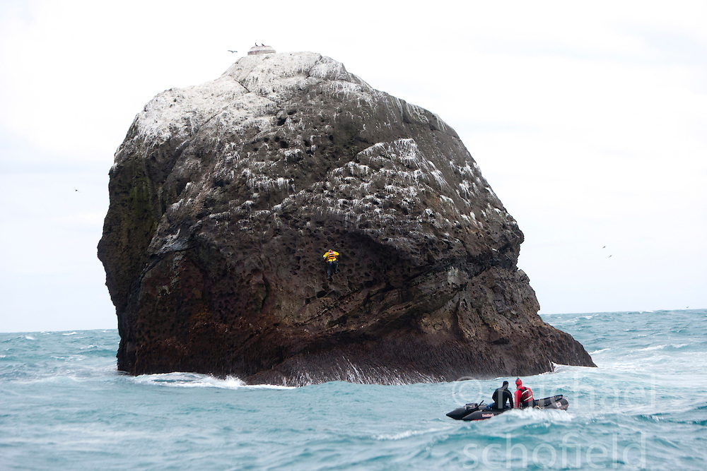 Nick Sharpe (red) in the small boat watches Nick Hancock (yellow) as he  heads down from the top of Rockall, after his reconnaissance mission for a future 60 day occupation of Rockall. The Rockall Jubilee Expedition, a unique endurance expedition to be undertaken by Nick, in order to raise funds for Help for Heroes .©Michael Schofield..