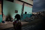 A woman walks past the Topolino building, one of the main shopping areas in downtown Port-au-Prince, Haiti, Wednesday, March 31, 2010.  Much of downtown was heavily damaged in the earthquake and many businesses have moved their operation to the street.