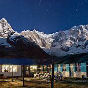 """Moonlight strikes Annapurna I (on the right, 26,545 feet), the world's 10th highest peak, seen from Annapurna South Base Camp (ABC, at 13,550 feet elevation) in the Annapurna Range of Nepal. On the left is Annapurna South, which appears higher in this perspective because it is closer.  Stars streak the sky, and the headlamps of motel residents make wavy lines of light as they pass by in the 3+minute time exposure. Panorama stitched from 2 images captured at 6:50pm October 27, 2007. Published in 2009 on Swedish trekking company site www.adventurelovers.se. Published in """"Light Travel: Photography on the Go"""" book by Tom Dempsey 2009, 2010."""