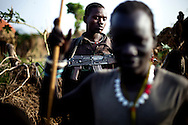 Jie warriors travel from their village to thier cattle camp to protect the women and children and possibly prepare for an attack on the Murle in Jonglei state, Southern Sudan.