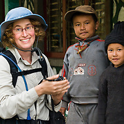 A trekker meets two Nepalese children at Ghandruk village (or Ghandrung, 6530 feet) in Nepal, in the Himalaya mountain chain, along the trail to Annapurna Sanctuary, Nepal, Asia. Published in September/October 2008 Sierra Magazine, Sierra Club Outings For licensing options, please inquire.