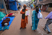 An Indian Sadhu (holi man) is seen holding a picture of Sai Baba on the morning of Shivaratri festival, on the street in Gokarna, Karnataka, India, on  February 17, 2015. Hindus across the country celebrate Mahashivratri, better known as Lord Shiva's wedding anniversary. Lord Shiva is also known as Nataraja, the Lord of Dancers.<br />
