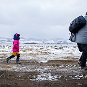2016 January–near Miratovac, Serbia. In subfreezing snowy weather, refugees walk the official-unoffical refugee crossing from the Tabanovce, Macedonia Train Station across the Serbian border.  A daily average of 2,400 refugees have crossed into Serbia throughout the winter.  Warmer months saw highs of 10,000 arrivals. Limited to what belongings they can carry with them, many have gone without food and water for extended periods. They have escaped their own country in conflict, taken a perilous boat ride from Turkey to Greece, and then moved onward through disorienting foreign lands in search of a peaceful home. Most refugees are headed to welcoming Germany. They are from  Afghanistan, Iraq, and Syria, with a wide range of socioeconomic backgrounds. Economic migrants also arrive in Macedonia and Serbia, but without the proper papers they are turned back, while some find smugglers to take them further into Europe.
