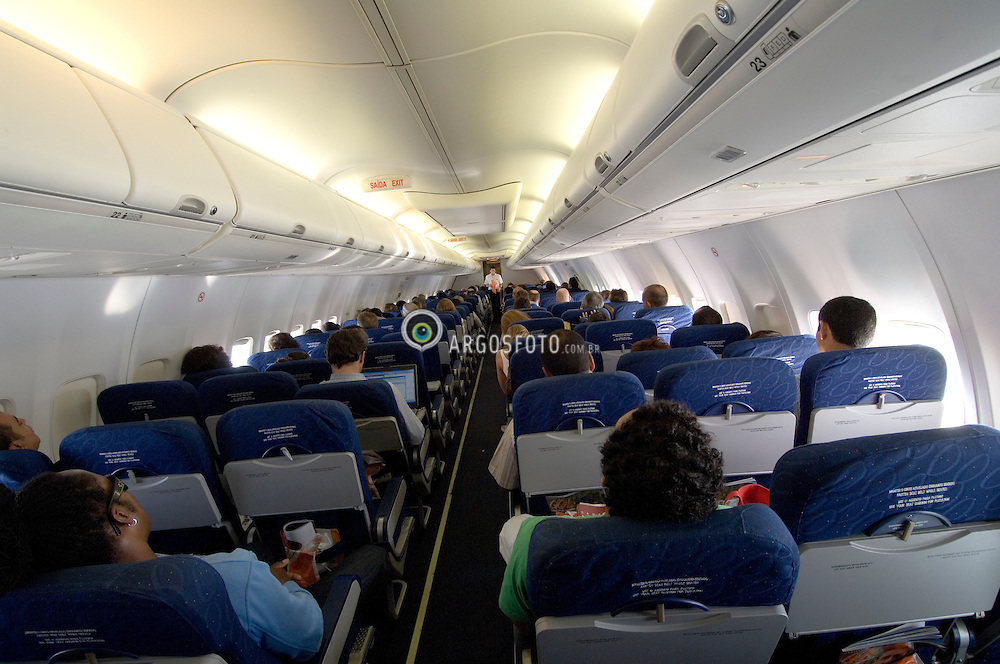Interior de aviao comercial mostrando os passageiros sentados (visao traseira) / Commercial Airplane inside showing the passagers sitten (back view)