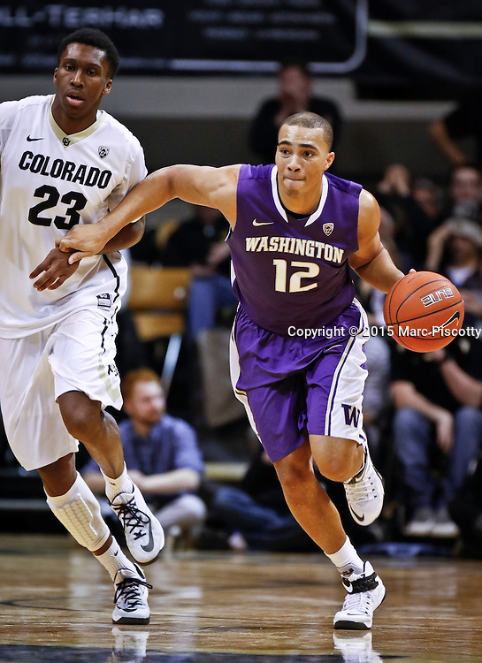 SHOT 1/22/15 10:00:07 PM - Washington's Andrew Andrews #12 pushes the ball upcourt in front of Colorado's Jaron Hopkins #23 during their regular season Pac-12 basketball game at the Coors Events Center in Boulder, Co. Washington won the game 52-50 on a shot with less than a second to play in the game. (Photo by Marc Piscotty / © 2015)