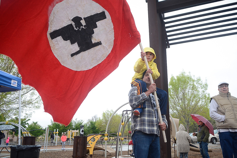 Gael Griego, 7, holds a National Farm Workers Association protest flag with his father Joaquin Griego while listening to Dolores Huerta, the activist who started the National Farm Workers Association with Cesar Chavez, speaks during the naming ceremony for Dolores Huerta Gateway Park before the annual Cesar Chavez Day march, Saturday, April 1, 2017, in Albuquerque, N.M. (Marla Brose/Albuquerque Journal)