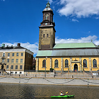 Landmarks along Norra Hamngatan in Gothenburg, Sweden <br /> This kayaker on the Great Harbor Canal is staring at the Christinae Kyrka clock tower which was named after Queen Kristina when it was finished in 1748. The yellow building on the right is the German Church&rsquo;s sanctuary. The neighboring building on the left along Norra Hamngatan or North Harbour Street was built in 1753. The Sahlgrenska House was the private residence of Brigitta Sahlgren.  She owned a huge sugary refinery and shipping business.
