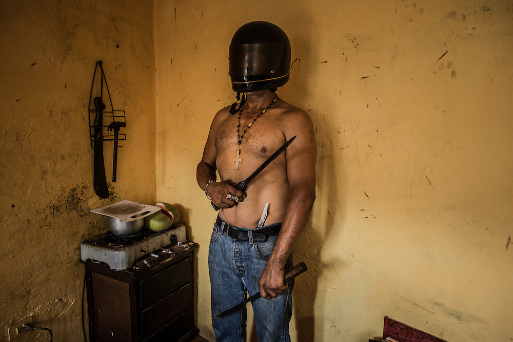 CARACAS, VENEZUELA - NOVEMBER 19, 2016:  Alexis Colina poses for a portrait in his one-bedroom home in Caracas, with the knives and motorcycle helmet he now uses to rob people. Before the crisis, Mr. Colina had a normal job and life, working as an auto mechanic - but when the economic crisis and hyperinflation caused his salary to lose so much value, that he could not even afford to feed his family, and shortages caused car parts to become nearly impossible to find - he turned to crime, robbing and selling drugs, to survive.  PHOTO: Meridith Kohut for The New York Times