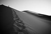 People climb a sand dune in the Gobi Desert, Mongolia.