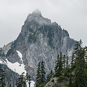 Kaleetan Peak (6259 ft / 1908 m) rises near Gem Lake in Alpine Lakes Wilderness Area in the Cascade Range of Washington, USA. In mid July, we hiked to Gem Lake 10 miles round trip with 2800 feet cumulative gain along Snow Lake Trail #1013 in Mt. Baker-Snoqualmie National Forest. Take Interstate 90 Exit #52 westbound or Exit #53 eastbound and follow signs to Alpental Road ski area parking lot and trailhead. To avoid crowds at this popular trail, start early and avoid sunny weekends. The trail down from the saddle viewpoint to Snow Lake is often snow covered through July 4.