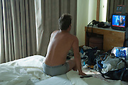 man at home in his underwear in a messy bedroom