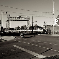 Biker rounding corner of street in Port Colborne, Ontario, Canada. Lift bridge in background. Ship travelling canal to right of picture