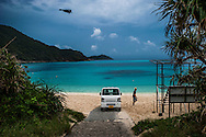Man collects beach umbrellas from Aharen Beach on Tokashiki Island as an afternoon storm looms and a black crow glides by.  Tokashiki Island, Kerama Archipelago, Okinawa Prefect, Japan.  The crystal clear coral seas are almost violet in color at Aharen.