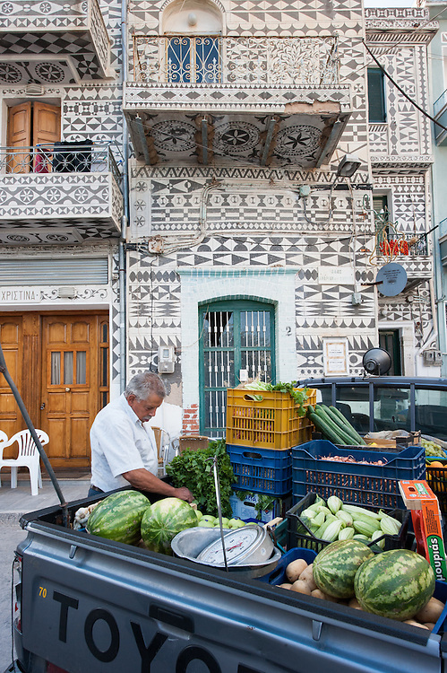 A wondering greengrocer selling vegetables and fruits from the back of his pick up track parked in a street in Pyrgi, Chios. In the background a typical local house with the decorative motives in the facade- Xysta or sgraffito.<br /> <br /> Pyrgi in Chios is known as the &quot;painted village&quot; on account of the decoration of the houses. The village still keeps its medieval style and together with the other Mastichochoria (Mastic Villages) are in the list of the Intangible Cultural Heritage of Humanity of UNESCO