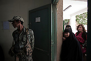 An Army soldier stands guard as Egyptians wait their turn to vote during the second day of the historic democratic Presidential election May 24, 2012 in the Imbaba district of Cairo Egypt. Coming 15 months after the revolution that toppled the regime of former President Hosni Mubarak, the election will determine not only the country's leader, but will shape the future role of the military, and the direction and pace of social and democratic reforms within the country. (Photo by Scott Nelson)