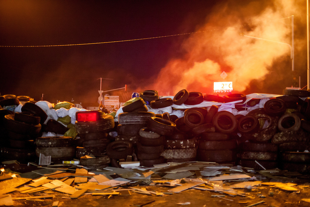 "Barricades blocking a building supplies store named ""Epicenter"" in the city of Lviv, Ukraine. The smoke comes out of barrels used for heating."