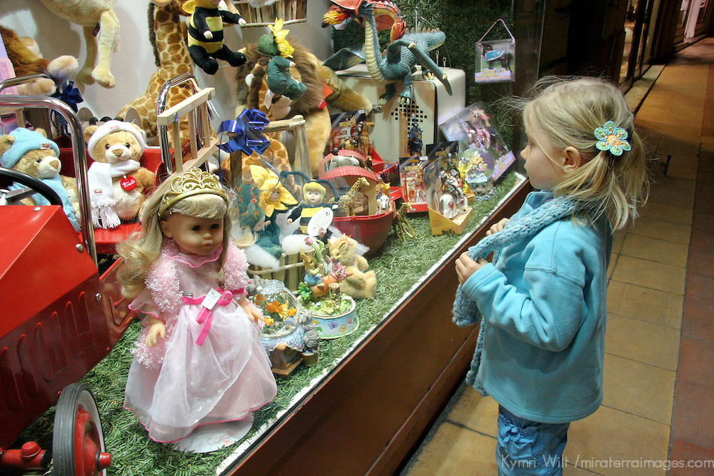 Europe, France, Menton. Little girl window shops for toys and dolls.