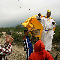 A healer and follower of Nino Fidencio, a curandero or healer who passed away in the 1938, throws candies to his followers just outside of Espinazo, Mexico on Thursday, October 19, 2006. Followers of Nino Fidencio believe that his spirit can posses other healers, who once possessed speak in child-like voices and perform a variety of medical cures on their followers.  His believers, an estimated 20,000, gather in his hometown for a three-day festival twice a year in March and October. (Photo/Scott Dalton)