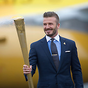 David Beckham the Olympic Torch to light a cauldron after the plane, also carrying Princess Anne and Locog chair Lord Coe, arrived at a Cornish air base..Flight BA2012, a gold-coloured A319 named The Firefly, was greeted at RNAS Culdrose by cheering crowds..After Friday's welcoming ceremony, the flame flies on Saturday to Land's End for the start of an 8,000 mile relay..The Princess Royal carried the transportation lantern containing the flame from the aircraft and on to the tarmac..It was transferred to a London 2012 torch and David Beckham lit a cauldron, to mark the flame's arrival on UK soil..© Antony Jones