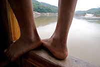 A worker stands on edge of a slow boat making its way along the Mekong River from Huay Xai to Luang Prabang, Laos.