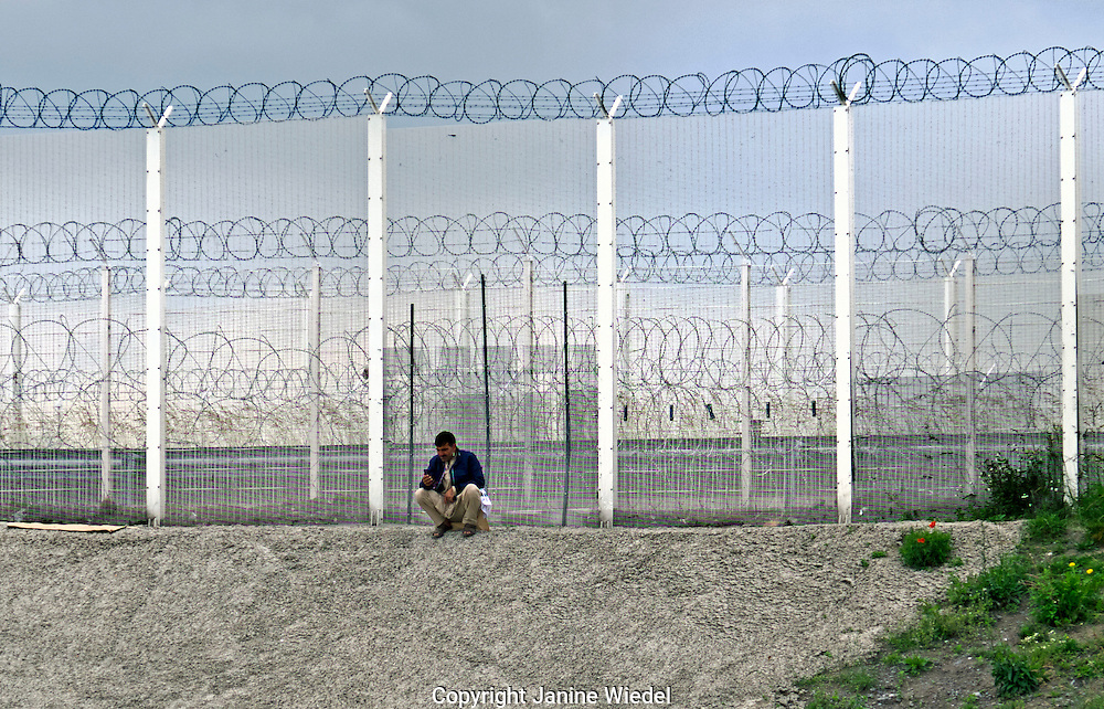 Razor wire perimeter fence separating the ferry port terminal from The Calais Jungle Refugee and Migrant Camp in France