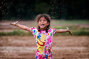Gammy, a Thai girl, takes time to play in the mud during rice planting season in Nakhon Nayok, Thailand. PHOTO BY LEE CRAKER