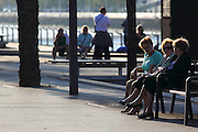 Old women sit on a bench on the Muelle de Evarista Churruco, the walkway along the River Nervión in Bilbao, on a sunny Sunday afternoon in October