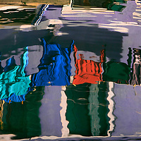 Just a typical sight in Burano: hanging clothes reflected in a waterway canal. Taken on a bright morning of december, with some beautifully warm light.
