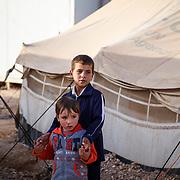 Ibrahim, 7, and Amir, 5, outside of their tent. Zaatari Camp for Syrian Refugees, Jordan, November 2013.