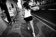 Raíca was born in Várzea Alegre, in Ceará state. She began to feel different from other boys at the age of 8 but only at age of 20 she left parental home and went to São Paulo, where she would make the changes in her body. Two men smile at Raíca while she walks back home after her training session at the gym.