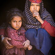 A Bakarwal, Gujjar mother and child sit together in their hut. Note the distinct hat and plats on the mother. Lidderwat, Kashmir, India