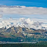 See Denali (20,310 feet or 6191 meters, aka Mount McKinley) from Kesugi Ridge Trail in Denali State Park, Alaska, USA. Denali is the highest mountain peak in North America, and measured from base to peak, it is earth's tallest mountain on land. Mount McKinley is a granitic pluton uplifted by tectonic pressure while erosion has simultaneously stripped away the somewhat softer sedimentary rock above and around it. Panorama stitched from 3 overlapping photos.