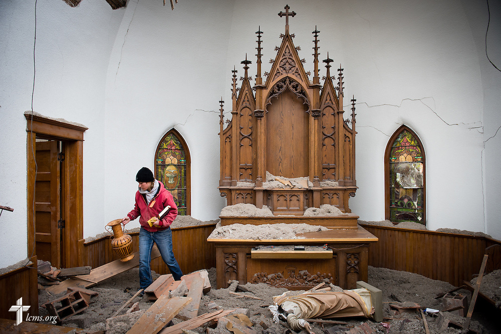 Kera Kaufman salvages cherished items next to the damaged altar and amongst the rubble of Zion Lutheran Church on Monday, May 11, 2015, in Delmont, S.D. A tornado swept through the area the previous day and destroyed the church and nearby buildings. LCMS Communications/Erik M. Lunsford