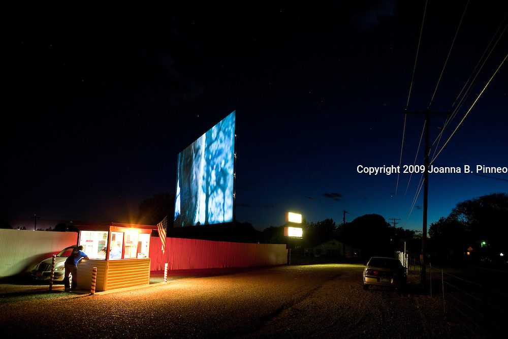"""At 8:30 p.m. a late customer pulls into the ticket stand at the Star Drive In  Montrose, Colorado.  """"Running the drive in is not a 'have to' situation. It is a passion, a love for, it's what we've be taught to do it's what we've done for so long I can't even imagine not doing it  and it is not a matter of dollars of cents it is a matter of what do we give to our community and in turn what our community gives back to us."""" Owner Pamela Friend."""