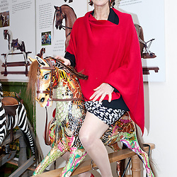 London, UK - 20 May 2013: Maureen Lipman sits on a rocking horse at the Stevenson Brothers stand  during the RHS Chelsea Flower Show 2013 edition press day.