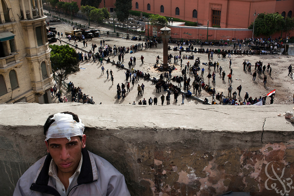 "An Egyptian anti-Mubarak protester sits atop a rooftop as fellow protesters watch for signs of approaching Mubarak supporters during a large demonstration dubbed the ""Day of Departure"" February 04, 2011 in Tahrir Square in Cairo, Egypt. The Egyptian military created a buffer zone between anti and pro Mubarak factions of protesters were able to prevent large scale clashes between the two sides that had taken place the past several days. ."