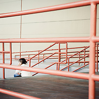 Person sitting on steps surrounded by red handrails