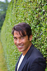 PhotoLibrary-14 Asian American man smiling and standing by a hedge in East Hampton, NY